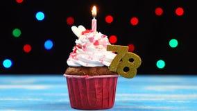 Queque delicioso do aniversário com vela e número de queimadura 78 no fundo borrado colorido das luzes filme