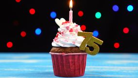 Queque delicioso do aniversário com vela e número de queimadura 75 no fundo borrado colorido das luzes video estoque