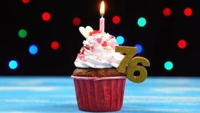 Queque delicioso do aniversário com vela e número de queimadura 76 no fundo borrado colorido das luzes vídeos de arquivo