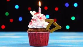 Queque delicioso do aniversário com vela e número de queimadura 77 no fundo borrado colorido das luzes filme