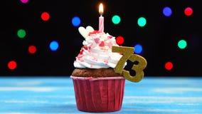 Queque delicioso do aniversário com vela e número de queimadura 73 no fundo borrado colorido das luzes filme