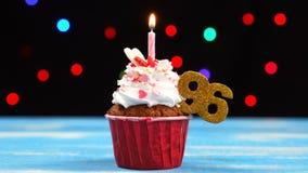 Queque delicioso do aniversário com vela e número de queimadura 96 no fundo borrado colorido das luzes filme