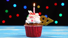 Queque delicioso do aniversário com vela e número de queimadura 97 no fundo borrado colorido das luzes video estoque