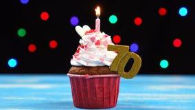 Queque delicioso do aniversário com vela e número de queimadura 70 no fundo borrado colorido das luzes filme