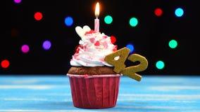 Queque delicioso do aniversário com vela e número de queimadura 42 no fundo borrado colorido das luzes vídeos de arquivo