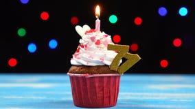 Queque delicioso do aniversário com vela e número de queimadura 71 no fundo borrado colorido das luzes filme