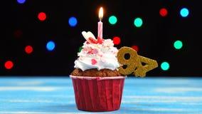Queque delicioso do aniversário com vela e número de queimadura 94 no fundo borrado colorido das luzes vídeos de arquivo