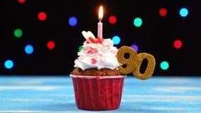 Queque delicioso do aniversário com vela e número de queimadura 90 no fundo borrado colorido das luzes video estoque