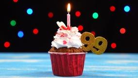 Queque delicioso do aniversário com vela e número de queimadura 99 no fundo borrado colorido das luzes filme