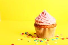 Queque do aniversário com creme da manteiga no fundo amarelo Fotografia de Stock
