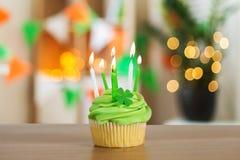Queque verde com seis velas ardentes na tabela fotos de stock