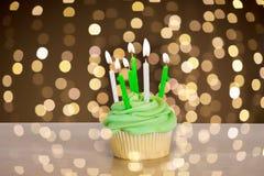 Queque verde com seis velas ardentes na tabela foto de stock