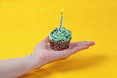 Queque verde e uma vela do aniversário na mão Foto de Stock