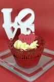 Queque vermelho de veludo com geada da baunilha e corações vermelhos bonitos com mensagem do amor Foto de Stock Royalty Free