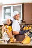 Queques asiáticos do cozimento dos pares na cozinha home Imagens de Stock Royalty Free