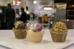 Queques: baunilha, chocolate, café em uns copos decorativos Fotos de Stock