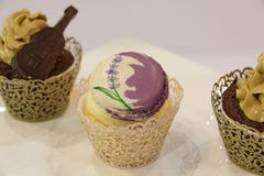 Queques: baunilha, chocolate, em uns copos decorativos Foto de Stock
