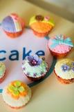 Queques bonitos, coloridos, deliciosos na tabela Fotos de Stock Royalty Free