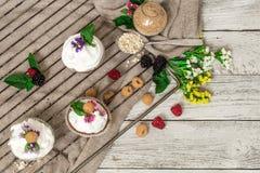 queques bonitos com as bagas no mel de madeira das porcas do fundo Imagem de Stock Royalty Free