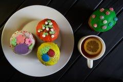 Queques coloridos - bolos da P?scoa em uma placa branca em um fundo preto homemade Luz do dia imagem de stock royalty free