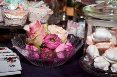 Queques coloridos e arranjo com rosas Imagem de Stock Royalty Free