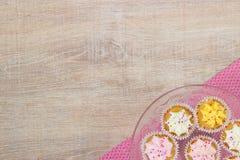 Queques coloridos em um fundo de madeira da tabela fotos de stock