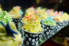Queques coloridos geados com uma variedade de sabores da geada Fotos de Stock Royalty Free