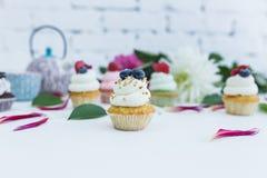 Queques com as flores e folhas frescas das bagas, um copo do chá ou café e uma chaleira Imagens de Stock Royalty Free