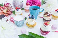 Queques com as flores e folhas frescas das bagas, um copo do chá ou café e uma chaleira Fotografia de Stock Royalty Free