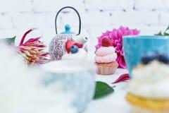 Queques com as flores e folhas frescas das bagas, um copo do chá ou café e uma chaleira Imagens de Stock