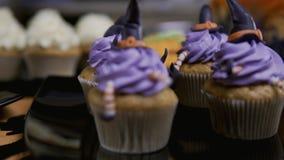 Queques com chapéu e pés da crosta de gelo O queque delicioso gosta da bruxa Conceito de Halloween video estoque