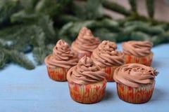 Queques com creme do chocolate em um fundo de madeira azul Imagem de Stock Royalty Free