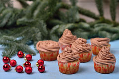 Queques com creme do chocolate em um fundo de madeira azul Fotos de Stock Royalty Free