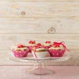 Queques com a crosta de gelo branca decorada com doces e as fitas cor-de-rosa Fotos de Stock Royalty Free