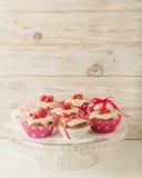 Queques com a crosta de gelo branca decorada com doces e as fitas cor-de-rosa Imagens de Stock