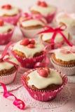 Queques com a crosta de gelo branca decorada com doces e as fitas cor-de-rosa Foto de Stock Royalty Free