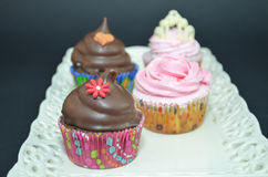 Queques com a decoração do molho e da flor de chocolate Imagens de Stock Royalty Free