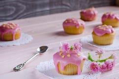 Queques com a geada cor-de-rosa na tabela Foto de Stock