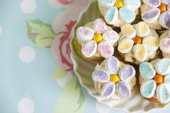 Queques decorados com as flores do creme e do marshmallow da manteiga fotografia de stock royalty free