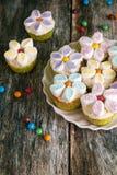 Queques decorados com as flores do creme e do marshmallow da manteiga foto de stock
