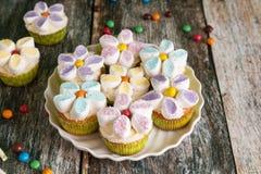 Queques decorados com as flores do creme e do marshmallow da manteiga imagens de stock royalty free