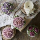 Queques decorados com flores de creme fotografia de stock