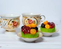 Queques decorados com frutos para a sobremesa e os dois copos da bebida Fotos de Stock