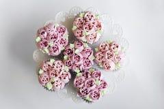 Queques decorados cor-de-rosa gourmet na tabela Fotografia de Stock Royalty Free