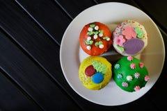 Queques deliciosos, coloridos - bolos da P?scoa em uma placa branca em um fundo preto homemade Luz do dia imagem de stock royalty free