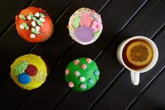 Queques deliciosos, coloridos - bolos da P?scoa em uma superf?cie de madeira preta e um copo do ch? com uma fatia de lim?o Caf? d fotos de stock