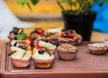 Queques deliciosos diferentes decorados com caramelo e as bagas frescas imagens de stock