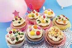 Queques do aniversário com balões em um fundo azul Foto de Stock Royalty Free