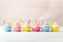 Queques do aniversário com velas no fundo de madeira branco Imagem de Stock