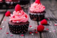 Queques do chocolate com creme cor-de-rosa, corações do açúcar e as framboesas frescas para Valentine Day Fotografia de Stock